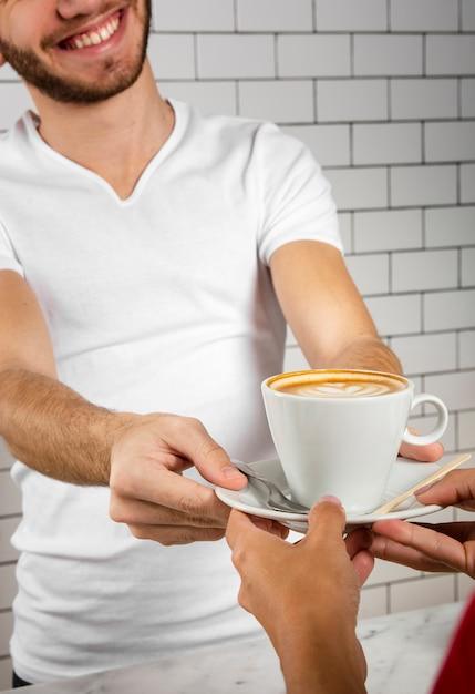 Jeune Homme Offrant Une Tasse De Cappuccino Photo gratuit