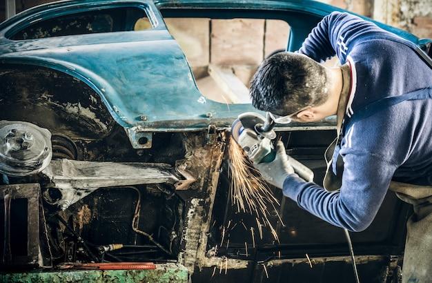 Jeune homme, ouvrier mécanique, réparation, vieux, voiture ancienne, carrosserie, à, griller électrique, dans, désordre, garage Photo Premium