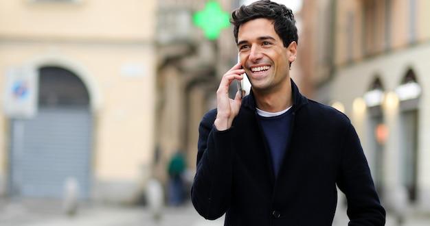 Jeune homme parlant au téléphone en plein air Photo Premium