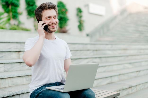 Jeune homme parlant au téléphone et utilisant un ordinateur portable pour un travail indépendant Photo Premium