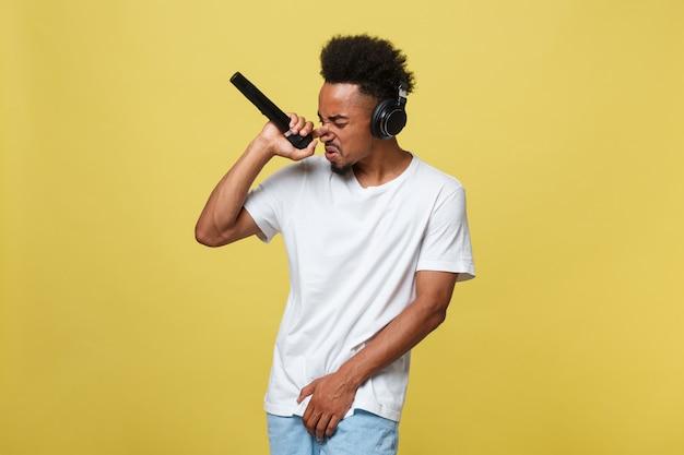 Jeune homme à la peau foncée avec une coupe de cheveux afro en t-shirt blanc, gesticulant avec les mains Photo Premium