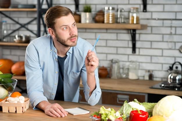Jeune Homme Pensif écrit La Recette En Cuisine Avec Stylo Et Journal Photo gratuit
