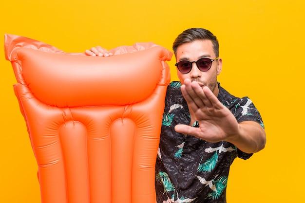 Jeune homme philippin tenant un lit gonflable Photo Premium