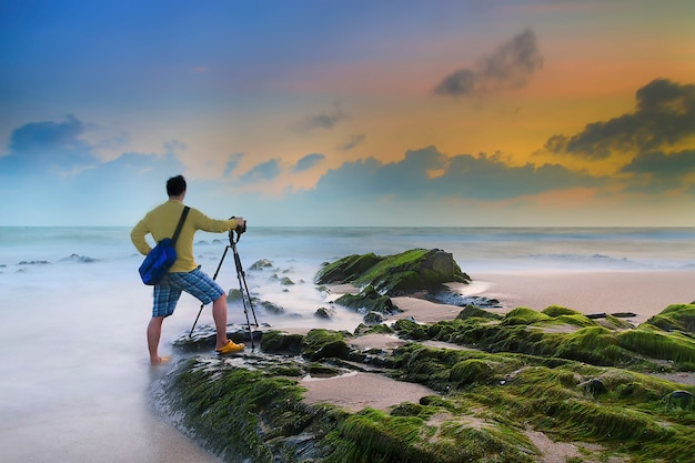 Jeune homme photographiant avec trépied sur la plage après le coucher du soleil Photo Premium