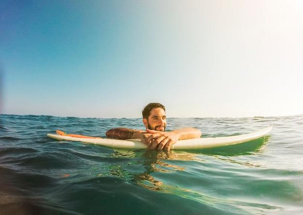 Jeune homme avec une planche de surf dans l'eau bleue Photo gratuit