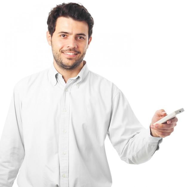 Jeune homme pointant avec une télécommande sur fond blanc Photo Premium