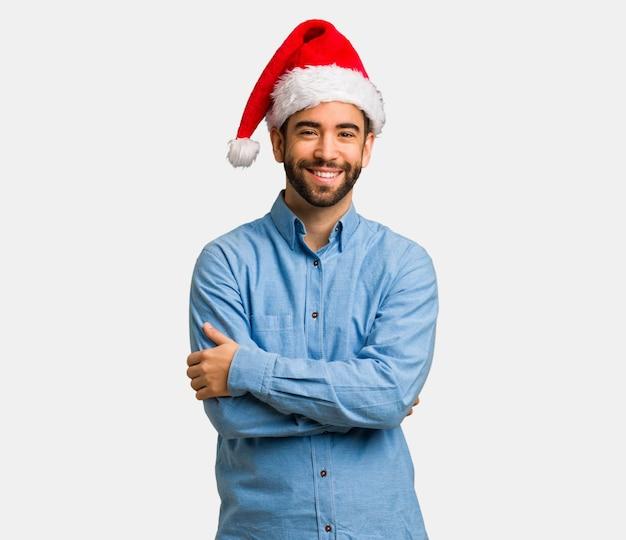 Jeune homme portant le bonnet de noel croisé les bras, souriant et détendu Photo Premium