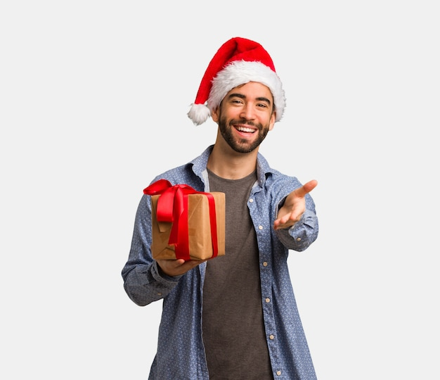 Jeune homme portant le bonnet de noel tendre la main pour saluer quelqu'un Photo Premium