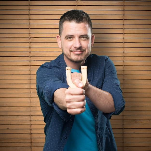 Jeune homme portant une tenue bleue. l'utilisation d'un lance-pierre. désignant Photo gratuit