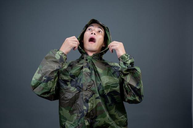 Le jeune homme porte un imperméable de camouflage et montre différents gestes. Photo gratuit