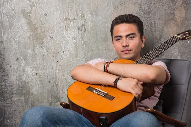 Jeune Homme Posant à La Caméra Tout En Saisissant La Guitare. Photo gratuit