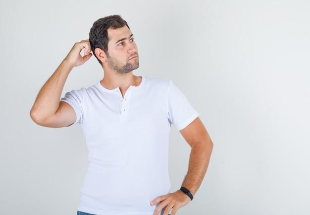 Jeune Homme Posant Avec Les Mains Sur La Taille Et Le Cou En T-shirt Blanc Photo gratuit