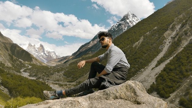 Jeune Homme Posant Avec Les Montagnes Photo gratuit