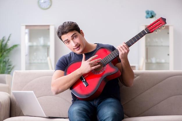 Jeune homme pratiquant la guitare à la maison Photo Premium