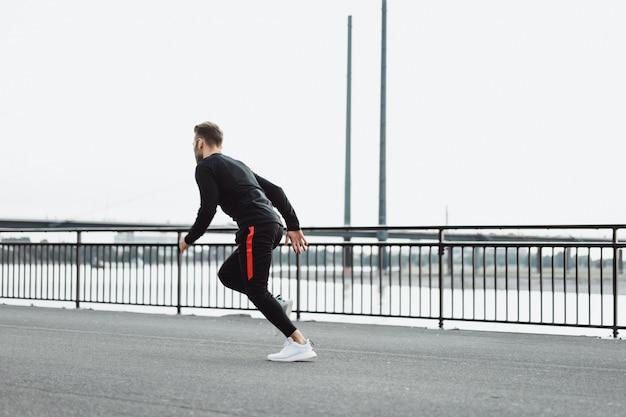 Jeune homme pratiquant des sports dans une ville européenne. sports en milieu urbain. Photo gratuit