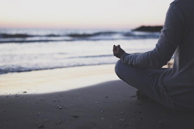 Jeune homme pratique le yoga sur la plage au coucher du soleil. Photo Premium