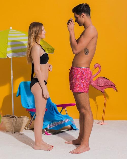 Jeune homme prenant des photos de sa petite amie en bikini en studio Photo gratuit