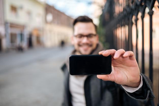 Jeune Homme Prenant Selfie Dans La Ville, Concentrez-vous Sur Le Premier Plan. Photo Premium