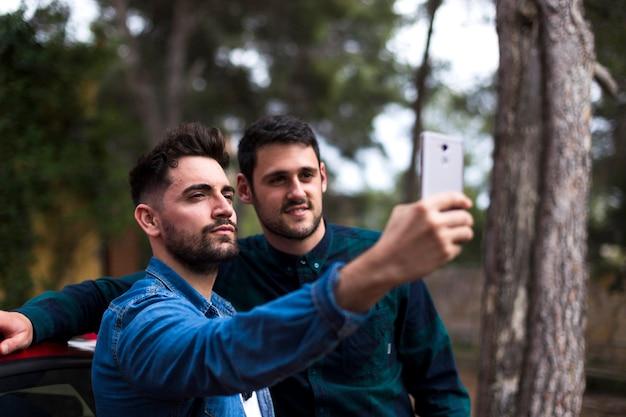 Jeune homme prenant selfie sur téléphone mobile avec son ami Photo gratuit