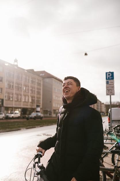 Jeune Homme Prend Son Vélo Sur Le Parking Photo gratuit