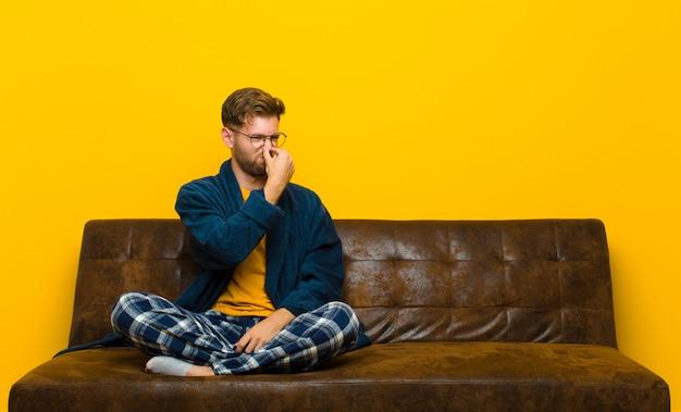 Jeune homme en pyjama se sentant dégoûté, tenant le nez pour éviter de sentir une odeur nauséabonde et déplaisante Photo Premium