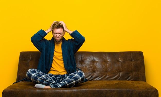 Jeune homme en pyjama se sentant stressé et frustré, les mains en l'air, fatigué, malheureux et souffrant de migraine. assis sur un canapé Photo Premium