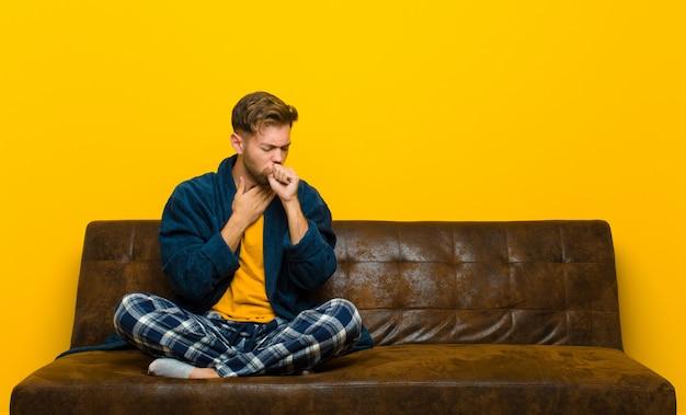 Jeune homme en pyjama souffrant de maux de gorge et de grippe, toussant avec la bouche couverte. assis sur un canapé Photo Premium