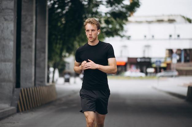 Jeune homme qui court dans la ville le matin Photo gratuit
