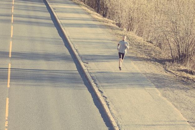 Jeune homme qui court dehors le long d'une route de montagne vide Photo Premium