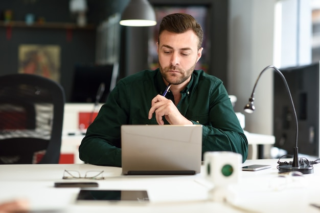 a76702028a Jeune homme qui étudie avec un ordinateur portable sur un bureau ...