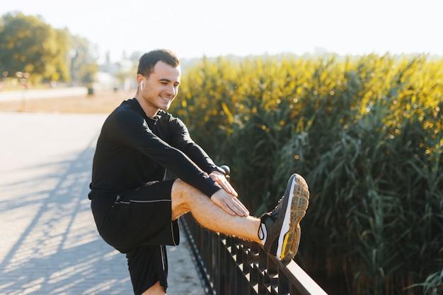 Jeune Homme Qui S'étend à L'extérieur Dans Le Parc Après Quelques Cercles De Course. Photo Premium