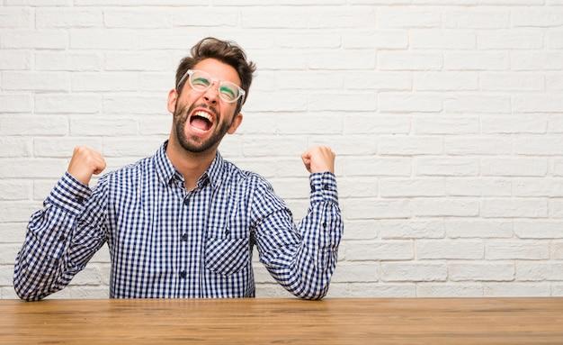 Jeune homme de race blanche assis très heureux et excité, levant les bras, célébrant une victoire ou un succès Photo Premium