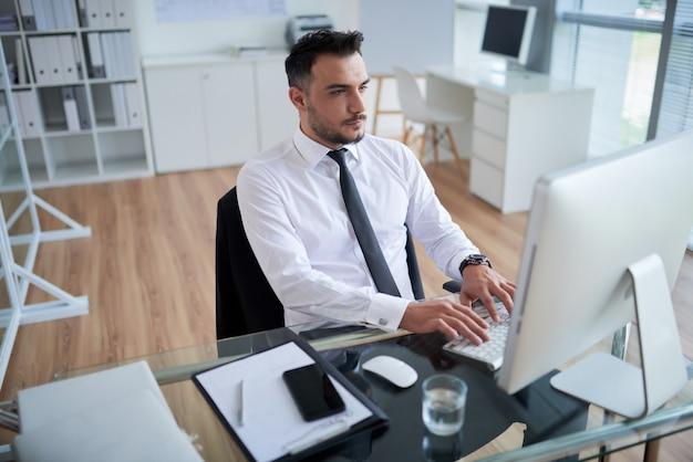 Jeune Homme De Race Blanche En Chemise Et Cravate Formelle Assis Dans Le Bureau Et Travaillant Sur Ordinateur Photo gratuit