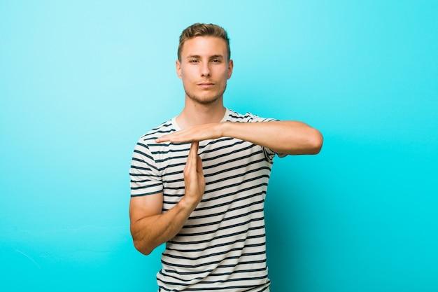 Jeune homme de race blanche contre un mur bleu montrant un geste de délai d'attente. Photo Premium