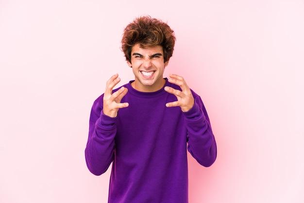 Jeune Homme De Race Blanche Contre Un Mur Rose Bouleversé Crier Avec Les Mains Tendues. Photo Premium