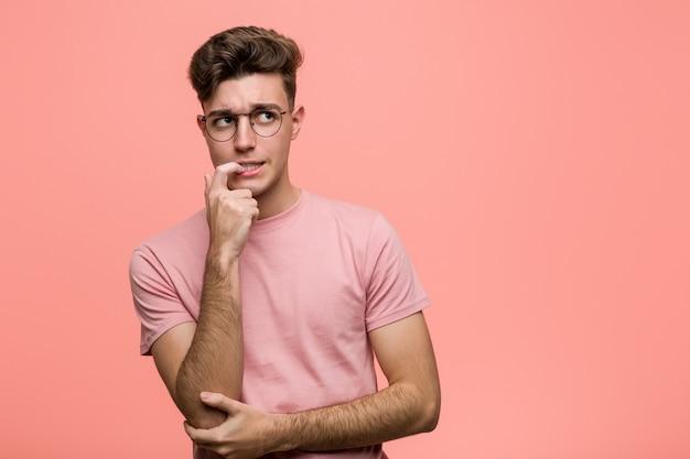 Jeune homme de race blanche cool détendu pensant à quelque chose en regardant un espace de copie. Photo Premium