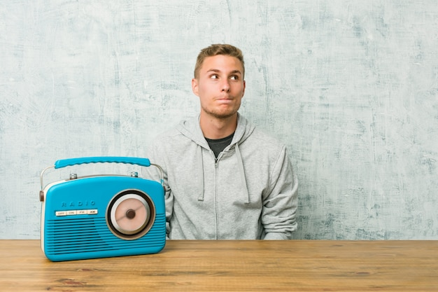 Jeune homme de race blanche à l'écoute de la radio, confus, douteux et incertain. Photo Premium