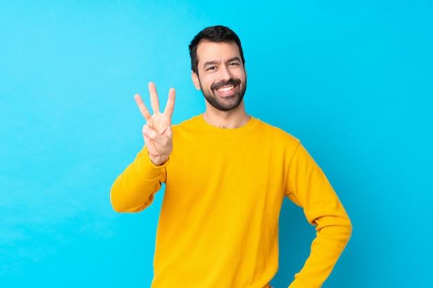 Jeune Homme De Race Blanche Sur Mur Bleu Isolé Heureux Et En Comptant Trois Avec Les Doigts Photo Premium