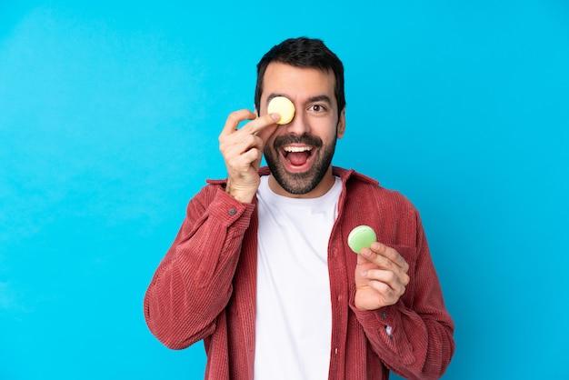 Jeune Homme De Race Blanche Sur Un Mur Bleu Isolé Tenant Des Macarons Français Colorés Photo Premium