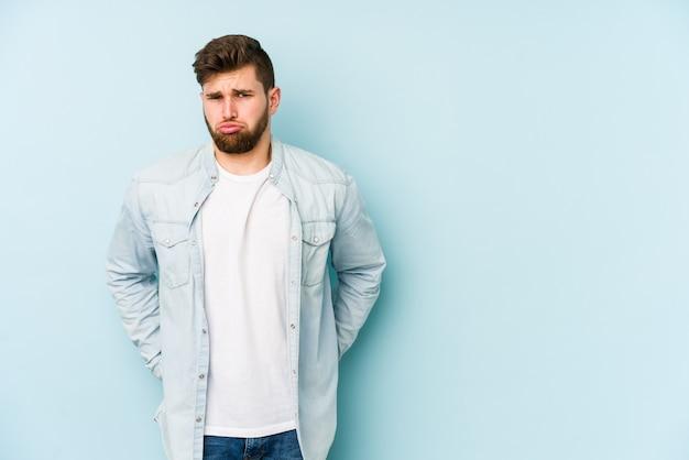 Jeune Homme De Race Blanche Sur Le Mur Bleu Souffle Les Joues, A Une Expression Fatiguée Photo Premium