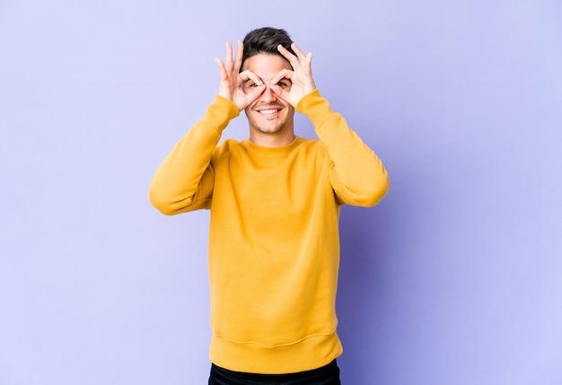 Jeune Homme De Race Blanche Sur Un Mur Violet Montrant Un Signe Correct Sur Les Yeux Photo Premium