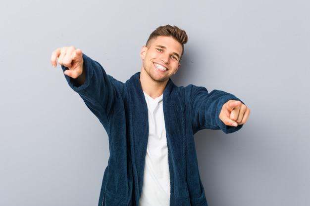 Jeune homme de race blanche portant des sourires joyeux pyjama pointant vers l'avant. Photo Premium