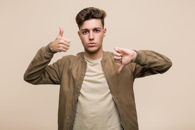 Jeune homme de race blanche portant une veste marron montrant les pouces vers le haut et le bas, difficile de choisir Photo Premium