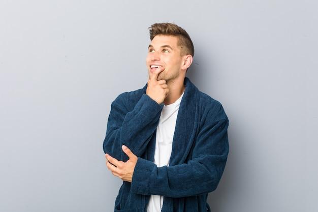 Jeune homme de race blanche en pyjama détendu pensant à quelque chose en regardant un espace de copie. Photo Premium