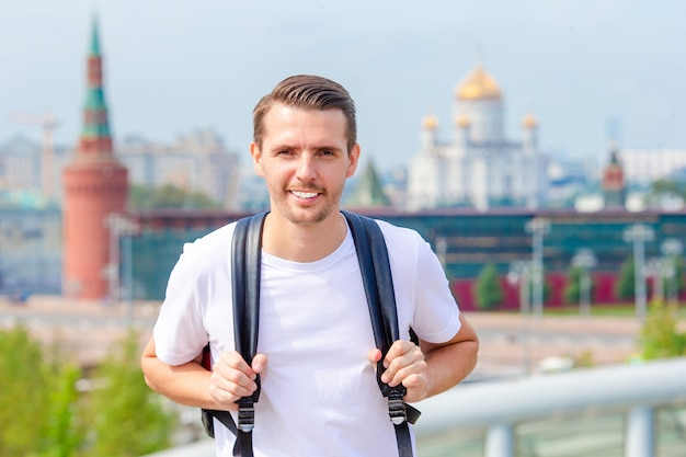 Jeune homme en randonnée souriant souriant portrait heureux. randonneur marchant dans la ville Photo Premium