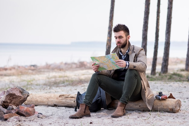 Jeune homme randonneur assis sur la plage au-dessus du rondin en regardant la carte Photo gratuit
