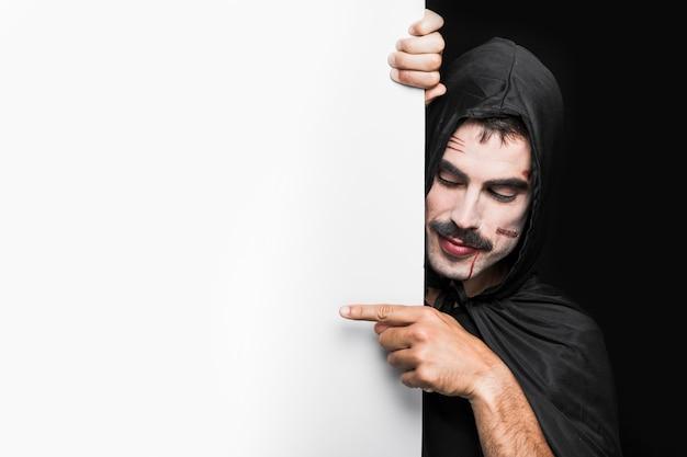 Jeune homme avec des rayures sur le visage en manteau noir avec capuche qui pose en studio Photo gratuit
