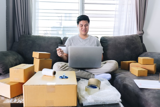 Un jeune homme a reçu des boîtes d'ouverture de magasinage en ligne et des articles achetés par carte de crédit, marketing en ligne sur bon de commande Photo Premium