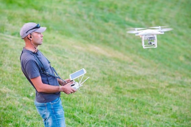 Jeune Homme Regardant Et Naviguant Sur Un Drone Volant Photo Premium