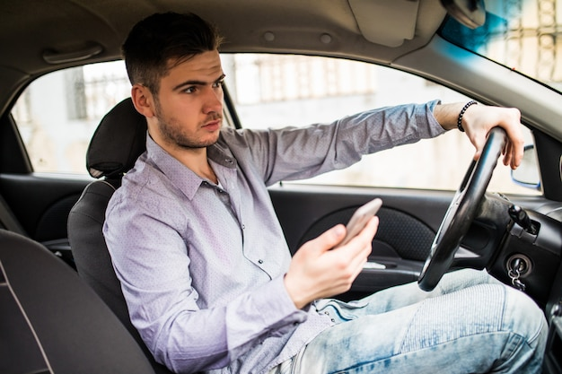 Jeune Homme Regardant Un Téléphone Mobile En Conduisant Une Voiture. Photo gratuit